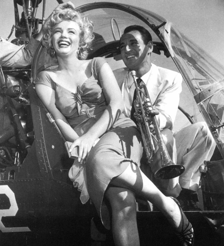 """On termine cette année 1952, qui fut riche en évènements et pour la notoriété montante de Marilyn grâce à son dernier film """"Niagara"""", avec la fête du musicien Ray ANTHONY (The Ray ANTHONY party) / La fête s'est tenue dans une villa de Sherman Oaks, dans le district de Los Angeles, situé dans la vallée de San Fernando. Marilyn, vêtue de la robe rouge du film """"Niagara"""", est arrivée en hélicoptère, puis s'est prêtée au jeu des photographes en faisant mine de jouer de la trompette et de la batterie sous les yeux avisés de Ray ANTHONY et de Mickey ROONEY, pendant que Ray ANTHONY chantait une chanson spécialement dédiée à Marilyn pour cette occasion, intitulée """"My Marilyn"""" . Parmi les nombreux convives, se trouvait aussi Sammy DAVIS Jr. Puis elle a rencontré le chien de la série """"Lassie"""". Les photographes présents: Bob WILLOUGHBY (qui a prit la plupart des photographies), Leni CARLSON et Phil STERN."""