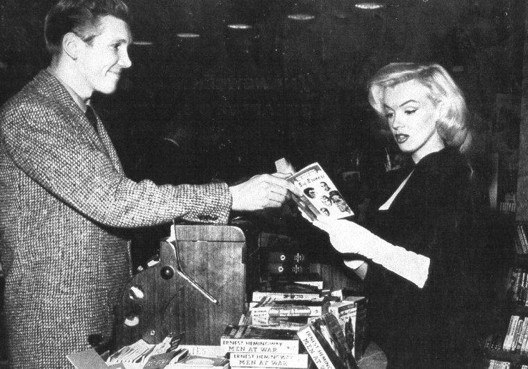 1953, Marilyn dans une librairie sous l'oeil de son ami et photographe André De DIENES... La journée se poursuivra avec l'invitation au mariage de la chroniqueuse Sheilah GRAHAM ; Marilyn sera alors accompagnée d'un autre ami, écrivain, scénariste et producteur, Sidney SKOLSKY.