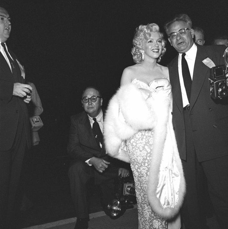 """Coiffure réussie, maquillage parfait et robe sublime, jamais Marilyn a été autant en beauté lors d'une Première / Le 4 novembre 1953, a lieu la première du film """"How to marry a millionaire"""" (Comment épouser un milionnaire) au """"Fox-Wilshire Theater"""" à Hollywood. Le film est tourné en cinémascope couleur et l'événement est fortement médiatisé par la présence de nombreux journalistes, reporters et photographes; ainsi qu'une foule de badaux qui sont sur place. De nombreuses personnalités assistent à la première : Robert MITCHUM, Debbie REYNOLDS, Mitzi GAYNOR, Rock HUDSON, Shelley WINTERS. Les participants au film arrivent en voiture seul ou par deux : le réalisateur Jean NEGULESCO est accompagné de sa femme ; Lauren BACALL est aux bras d'Humphrey BOGART ; puis le scénariste Nunnally JOHNSON avec Marilyn. Ils posent avec plaisir pour les photographes et Marilyn se montre plus que jamais disponible autant envers les journalistes, répondant aux micros des reporters, mais aussi des photographes en posant longuement, que du public composé d'anonymes, en signant des autographes."""