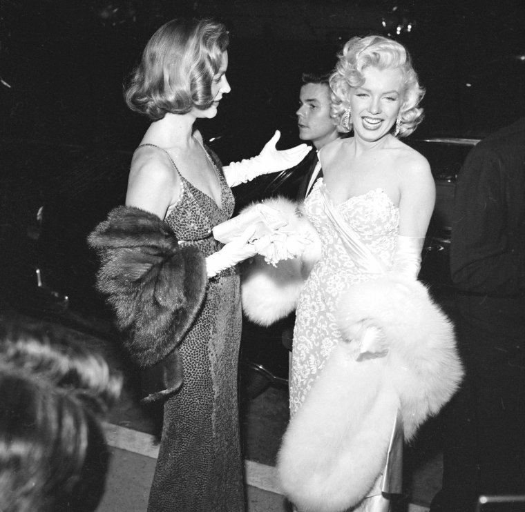 """1953 PREMIERE du film """"How to marry a millionaire"""" (Comment épouser un millionnaire) de Jean NEGULESCO / ANECDOTE / Nunnally JOHNSON se souvient d'une soirée plutôt désopilante : """"Dès son arrivée chez nous (chez JOHNSON et sa femme), Marilyn demande un bourbon-soda. Puis, alors que pourtant nous devions dîner tôt et légèrement, elle en demande un autre. Elle était à la fois surexcitée et très angoissée à la perspective de cette soirée. Je ne la savais pas à ce point naïve et spontanée; et je fus stupéfait de voir l'importance qu'elle accordait à cette première: pour elle, c'en était presque insupportable. Nous nous préparons à monter dans la voiture -une limousine louée, avec chauffeur- et elle demande un troisième verre, sans soda cette fois. Gentlemen jusqu'au bout, BOGART et moi bûmes avec elle pendant le trajet. Il n'y avait pas trio plus aimable que nous dans tout l'Etat de Californie quand nous fîmes notre entrée dans le théâtre (...). Pour tout dire, elle était complètement paf. Au moment même où le film commençait, il a fallu qu'elle aille aux toilettes. Ma femme l'a accompagnée car il était clair que Marilyn avait besoin d'aide. Ronde comme elle était dans une robe ultra étroite, qu'elle s'était faite coudre sur elle. Ce n'a pas été rien, je vous assure (ma femme m'a raconté la scène après), de lui faire faire pipi, puis de la remettre dans un état convenable pour qu'elle retourne à sa place. Quand on se fait coudre dans sa robe, on ne devrait jamais trop boire."""""""