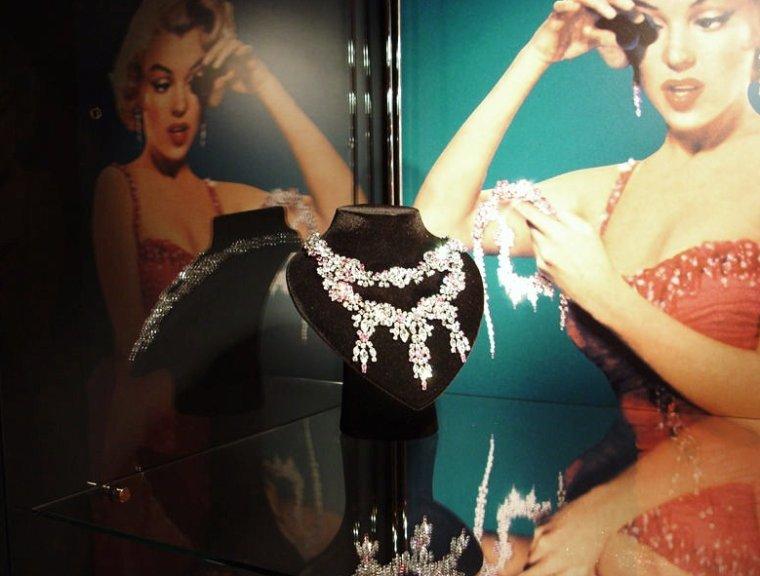 """1953 photo publicitaire pour le film """"Gentlemen prefer blondes"""" de Howard HAWKS / DIAMANTS / Il va de soit que dans le film Marilyn ne porte pas de vrais diamants, même si elle le chante suavement dans sa chanson """"Diamonds are a girl's best friends"""" ; Il se trouve que les fameux diamants sont faits en cristal de SWAROVSKI / SWAROVSKI est le nom de marque pour les produits en cristal (verre au plomb) qui sont produits par les entreprises appartenant à """"SWAROVSKI International Holdings"""". C'est un équivalent moderne de ce qui était connu autrefois en France sous le nom de « strass », l'autre verre au plomb porté par les gens d'opéra et les danseurs de cabaret. Fondé en 1895, l'atelier SWAROVSKI est devenu un géant du secteur du cristal, développant une stratégie commerciale destinée à faire assimiler des créations peu coûteuses à d'authentiques bijoux à la mode. Le groupe possède au début 2008, 1 343 boutiques dans 120 pays, dont 96 ont été ouvertes en 2008. L'effectif global dépasse 22 000 personnes, dont 6 700 à Wattens, dans la vallée du Tyrol (Autriche) où il est le premier employeur. En 2007, le CA atteignait 2,56 milliards d'euros, soit le double d'il y a 10 ans, grâce à la vente de cristal (80%) et de verres d'optique (20%). Le logo de SWAROVSKI était l'edelweiss jusqu'en 1989, où il a été remplacé par le cygne. Ce logo est présent sur chaque création en gravure ou en sablage, bijou ou sculpture, gage d'authenticité et de technicité. Le catalogue propose actuellement 24 000 produits."""
