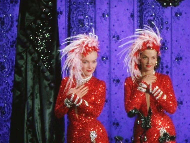 """LE FILM PEUT ENFIN COMMENCER... 1953, Marilyn et Jane RUSSELL chantant la chanson """"A little girl from a little rock"""" dans le film """"Gentlemen prefer blondes"""" (Les hommes préfèrent les blondes) de Howard HAWKS / Synopsis / Cette comédie musicale se situe dans le milieu des danseuses de revues. Le scénario joue sur l'opposition totale entre les caractères des deux danseuses vedettes : d'une part, Lorelei LEE (Marilyn) et d'autre part, Dorothy SHAW (Jane RUSSELL). La première, blonde naïve, n'est intéressée que par les hommes riches et le mot « diamant », la deuxième, brune à la repartie bien aiguisée, tombe toujours amoureuse d'hommes honnêtes mais peu fortunés, et ce au grand désespoir de son amie. Car malgré tout ce qui les oppose, ces deux jeunes femmes sont les meilleures amies du monde. Elles sont bien décidées à partir en France pour découvrir Paris. Ce voyage est organisé par Lorelei aux frais de son richissime futur époux, Gus ESMOND. Elle s'embarque sur un magnifique bateau avec Dorothy comme chaperon, toutes deux surveillées de près par un détective privé, Malone, engagé par le père de Gus."""