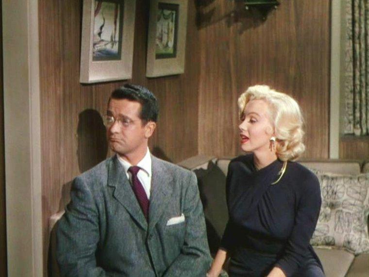 """1953 """"Gentlemen prefer blondes"""" (Les hommes préfèrent les blondes) de Howard HAWKS / CRITIQUE (part 5) / « Si nous ne parvenons pas à récupérer ses photos, nous ne méritons pas le nom de femmes », dit Dorothy à Lorelei, alors qu'elles viennent de comprendre que leur ami Malone est en fait un détective privé engagé par le père d'Esmond, le fiancé de Lorelei. Qu'est-ce donc que le pouvoir féminin, selon HAWKS ? Certainement celui de cacher son intelligence derrière des sourires envoûtants... « Faisons-leur croire que nous sommes stupides pour mieux les contrôler », tel est leur credo. Dorothy et Lorelei sont évidemment loin d'être idiotes : ce que les dialogues répètent à foison, et que la caméra de HAWKS accentue en faisant des hommes de parfaits crétins, ne pensant jamais avec leur cerveau. Voici Esmond, petit toutou à lunettes, que Lorelei peut convaincre de tout faire : « Monsieur Esmond a parfois beaucoup de mal à me résister », déclare-t-elle dans un sourire de connivence à son amie. Ou Sir Francis BEEKMAN, qui se fait appeler « Piggy » (« petit cochon ») et qui croit dur comme fer qu'une femme comme Marilyn puisse le trouver « moins vieux qu'elle le croyait ». Ou Malone, le détective, condamné à rentrer chez lui en peignoir rose après avoir perdu son pantalon, lestement retiré par les deux jeunes femmes. La gente masculine n'a pas beau jeu dans """"Les hommes préfèrent les blondes"""" : d'ailleurs, elle n'existe pas hors de la présence féminine. Il faut voir ainsi le groupe d'athlètes préparant les J.O., habillés d'horribles shorts couleur chair, se laisser piétiner ou arracher les cheveux par Dorothy. Seul le jeune Henry SPOFFORD III parvient à tirer son épingle du jeu. Mais il a... 10 ans. Gageons que pour HAWKS et ses scénaristes, les autres hommes du film n'en avaient pas beaucoup plus."""