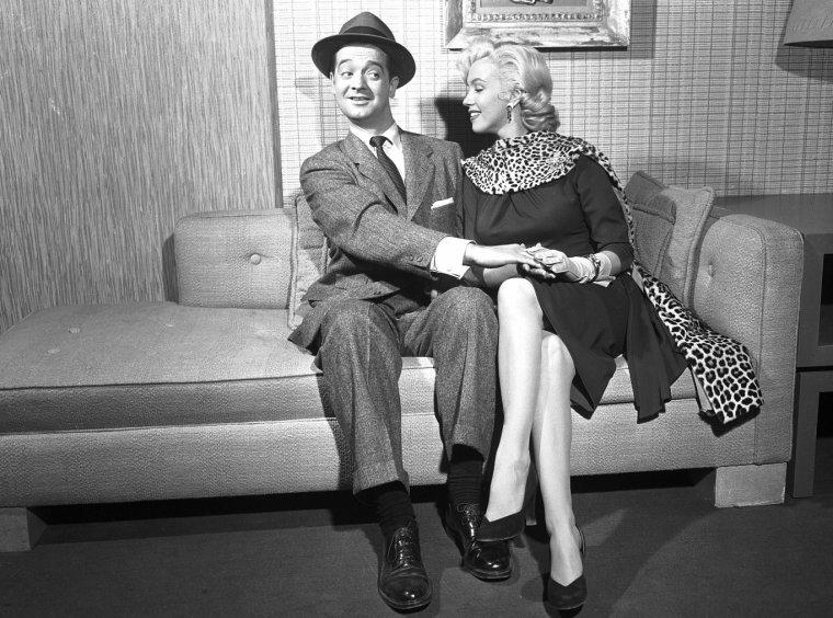 """1953 """"Gentlemen prefer blondes"""" (Les hommes préfèrent les blondes) de Howard HAWKS / CRITIQUE (part 6) / Cette satire des rapports hommes/femmes, où les dernières dominent clairement les premiers en tirant parti de leur désir incontrôlable, est agrémentée d'une sensualité exacerbée, où l'érotisme est tant sous-entendu qu'il éclate à chaque scène. HAWKS s'attarde sur le corps généreux de ses deux actrices, leurs jambes interminables ou sur leur tour de poitrine souligné par des robes plus moulantes les unes que les autres (et dont les couleurs vives tranchent sur les costumes noirs des hommes, mais accentuent aussi l'absence d'autres femmes). Des deux actrices, c'est évidemment Marilyn qui tire le mieux la couverture à elle. Jane RUSSELL était pourtant la star du film (ce qui fit dire à Marilyn : « Mais c'est moi la blonde ») ; mais Marilyn fit tant gagner son personnage en envergure, crevant l'écran de sa voix suave (l'actrice étant aussi, on l'oublie souvent, une incroyable chanteuse) et de sa démarche balancée reconnaissable entre toutes, qu'elle parvient à faire oublier la présence de sa co-star, et à ne pas faire mentir le titre du film. Lorsqu'elle étouffe un « Daddy » (« Papa ») à l'adresse de son amoureux, ce n'est plus Lorelei qui parle, mais Marilyn, qui devait se souvenir de ses débuts au cinéma (lorsqu'elle chanta « Everybody needs a Da-da-daddy »), mais aussi de sa propre vie amoureuse. Elle donne alors à son personnage sa sincérité et sa délicatesse d'actrice, consciente que si tout le monde voyait déjà en elle le symbole même de la blonde stupide, il lui revenait de s'en moquer et d'en jouer. La légende voudrait que ce fut l'actrice elle-même qui souffla aux scénaristes une des plus belles répliques du film (« Je peux être intelligente quand il faut, mais la plupart des hommes n'aiment pas ça ») : sans doute la légende a-t-elle bien une part de vérité.  Alors, HAWKS, cinéaste féministe ? Voilà bien un épitaphe qui ferait rire le vieil Howard, même de l"""