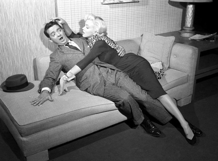 """1953 """"Gentlemen prefer blondes"""" (Les hommes préfèrent les blondes) de Howard HAWKS / COMMENTAIRE / C'est la première fois que l'immense réalisateur Howard HAWKS aborde la comédie musicale. Ce fut aussi la dernière car, bien que mélomane, le cinéaste avoua ne pas être à son aise dans le genre. Il laissera ainsi la Fox confier la mise en scène des numéros chantants et dansants au célèbre chorégraphe Jack COLE, qui imagina d'ailleurs une chorégraphie de la séquence des diamants jugée trop osée par le Studio (le spectateur ne perd toutefois rien au change car la scène, dans sa forme définitive, reste d'un allant, d'une grâce et d'une beauté affriolantes). HAWKS ne mit jamais les pieds sur le plateau où se réglaient les chorégraphies. La réussite de ces scènes viendra alors de l'apport conjugué de Jack COLE, du chef opérateur et du monteur du film. La légende qui veut que Howard HAWKS aie touché à tous les genres reste ainsi intacte, même si """"Les Hommes préfèrent les blondes"""" demeurera le film le moins personnel du réalisateur. Ce qui n'empêchera pas HAWKS d'ajouter son grain de sel à l'histoire, aux scènes principales et évidemment à la direction d'acteur."""