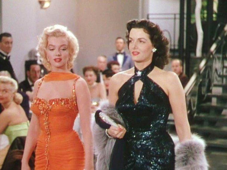 """1953 """"Gentlemen prefer blondes"""" (Les hommes préfèrent les blondes) de Howard HAWKS (photos de Marilyn sur le tournage et photos du film) / PETITE HISTOIRE / A la fin de la deuxième guerre mondiale, la Fox développe une politique de production misant le tout sur la plastique de ses actrices, blondes de préférence. Ainsi elle a très tôt pris sous contrat bon nombre de jeunes filles aux formes avantageuses et achète tous les scénarios pouvant les mettre en avant. L'adaptation sous forme de comédie musicale du livre culte de Anita LOOS (écrit en 1925 et déjà adapté en muet en 1928) qui arrive sur les bureaux des producteurs à la fin de l'année 1952 correspond parfaitement à ces critères. La Fox saute sur l'occasion et n'a plus alors qu'à piocher dans ses réserves pour trouver la brune et la blonde. En janvier 1953, Marilyn est à l'affiche du très remarqué """"Niagara"""", qui pulvérise immédiatement tous les records. Bien que la qualité du film laisse quelques fois à désirer, Marilyn y interprète quelques unes de ses meilleures scènes, et le rôle de Rose LOOMIS (une femme perverse et psychopathe à l'érotisme fumant, symbole sexuel par excellence) lui rapporte le prix """"Redbook"""" du meilleur espoir. Marilyn est au sommet du box-office lorsque La Fox la place dans le casting de sa nouvelle production. Pour faire le pendant de la blonde rêveuse aux jolies fesses, la firme jette son dévolu sur une brune terre à terre à jolie poitrine, aussi célèbre que la première, Jane RUSSELL. Devenue vedette internationale pour son opulente poitrine à la suite de la campagne publicitaire de son premier film """"The Outlaw"""" (1941) qui fut censuré dès sa sortie, elle a la notoriété adéquate pour former un duo de choc avec Marilyn..."""