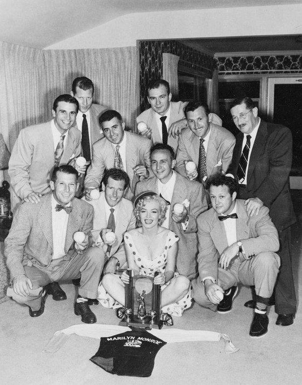 """Marilyn participe à la remise du prix du Studio """"League ChampionShip"""" d'un match de baseball organisé par les techniciens de la Fox de Los Angeles. Marilyn pose avec les joueurs et avec leurs épouses. Marilyn porte la même robe à poids qu'en 1952 à Atlantic-City lors de la rencontre des femmes militaires / La balle de baseball est signée par toute l'équipe mais aussi par Joe DiMAGGIO et Marilyn."""