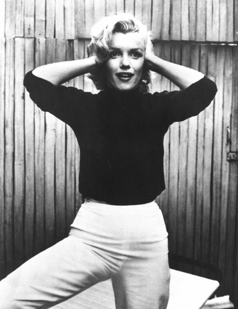 """1953, Marilyn pose dans la cour de son appartement sur Doheny Drive, puis lisant dans son salon, pour un reportage du magazine """"Life"""", sous l'oeil du photographe Alfred EISENSTAEDT / Né en Prusse-Occidentale, EISENSTAEDT déménagea avec sa famille à Berlin en 1906. Il combattit dans l'artillerie allemande pendant la Première Guerre mondiale. Il devint photographe professionnel en 1929. Quatre ans plus tard, il réussit à photographier une réunion entre Adolf HITLER et Benito MUSSOLINI en Italie. Tout d'abord accepté par les Nazis, il fut rapidement persécuté comme Juif et émigra aux États-Unis en 1935 et vécut à New York le restant de ses jours. EISENSTAEDT rejoignit, dès sa création, le magazine """"Life"""", dont il fut un photographe vedette de 1936 à 1972 et photographia les plus grandes vedettes telles Sophia LOREN, Ernest HEMINGWAY ou Marilyn. Il fit au total 90 couvertures pour """"Life"""". Le Prix """"Alfred-EISENSTAEDT"""" est décerné en son honneur par """"Life"""" et l'Université Columbia."""