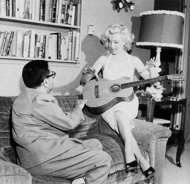 """1953,  deux séries de photos de Marilyn la montrant chez elle dans son appartement de DOHENY DRIVE dans la robe qu'elle portait au """"Grauman's Chinese Theatre"""" accompagnée par son ami journaliste, producteur, acteur... Sidney SKOLSKY pour la première série de photos et Marilyn et les livres, sa grande passion, en mini-short et polo / PHOTOS prisent par Bob BEERMAN."""