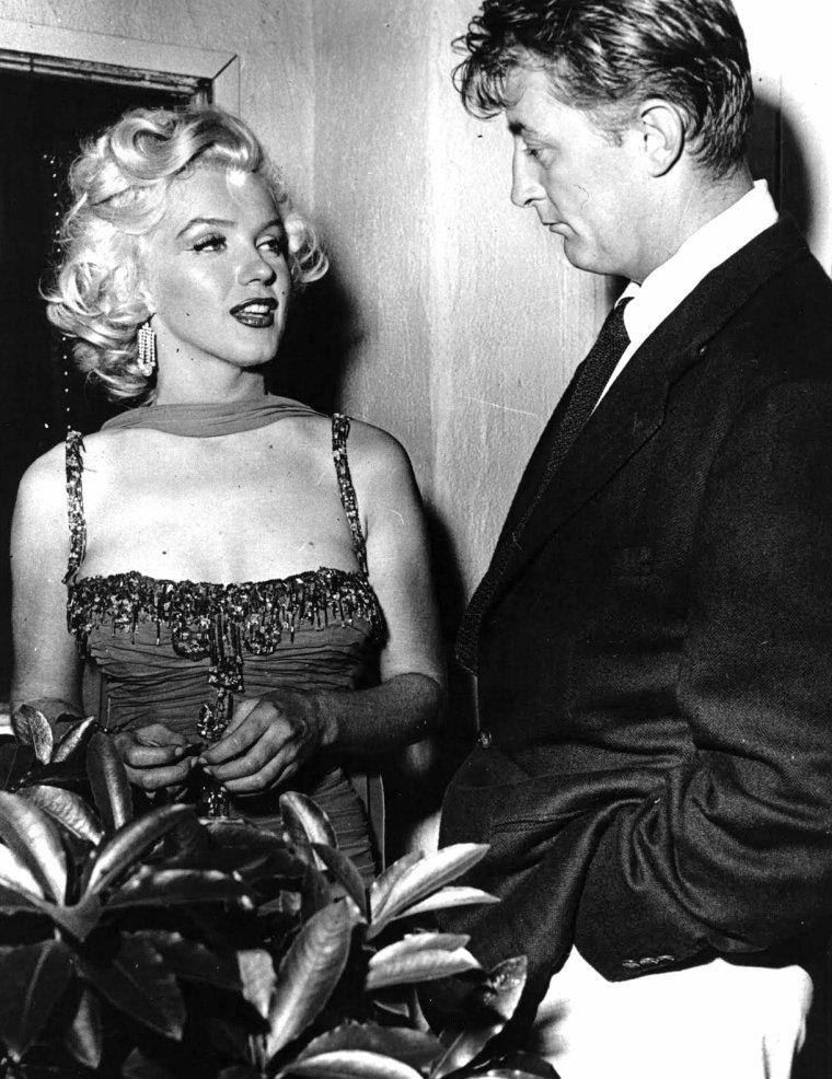"""Juillet 1953, c'est aux bras de Robert MITCHUM (qui sera son partenaire dans """"River of no return"""") que Marilyn arrive au """"Hollywood Bowl"""" afin de participer à une action caritative dont les bénéfices seront reversés à l'Hôpital """"Saint Jude""""... Parmi la liste des invités, on trouvera entre autres, Danny KAYE, Red BUTTONS ou encore le quatuor """"Ames Brothers"""", tout ça sous l'oeil du photographe Bruno BERNARD, dit """"Bernard of Hollywood"""" et de Danny THOMAS, acteur et présentateur d'un soir pour la soirée. (1ère photo). Pour l'occasion Marilyn porte une des robes signée TRAVILLA qu'elle avait dans le film """"Gentlemen prefer blondes""""."""