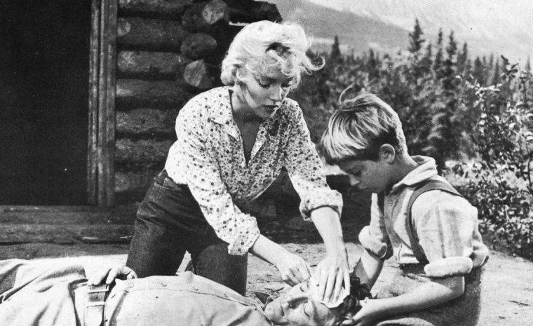 """1953 """"River of no return"""" (La rivière sans retour) d'Otto PREMINGER (Photos de tournage et photos du film) : ANALYSE et CRITIQUE (part 4) / Là réapparaît la """"Preminger's touch"""" : dans cette franchise sensuelle, dans cette transparence du style mettant à nus les corps comme les âmes. Matt CALDER n'est pas que l'icône d'une sagesse exemplaire jetée en pâture au regard admiratif de son fils ; c'est avant tout un homme au passé troublé par un incident tragique, tentant de se reconstruire, psychologiquement et physiquement. Et comme tout héros participant du mythe de Robert MITCHUM, c'est un homme qui ne se confie pas ; ni morphologiquement, ni bien sûr verbalement. Mais lorsqu'il se jette sur Marilyn pour l'immobiliser et la prendre de force au cours d'une séquence très peu suggestive qui évoque à plus d'un titre l'interception et la maîtrise de Dorothy DANDRIDGE par Harry BELAFONTE dans le futur """"Carmen Jones"""", c'est toute la dualité de son personnage, ses frustrations d'homme reclus par plusieurs années d'emprisonnement, qu'il exprime avec une évidence patente et indélébile. Et ce n'est que lorsque Mark aura appréhendé cette évidence et accepté son père avec ses forces et ses faiblesses, que son apprentissage filial sera achevé."""