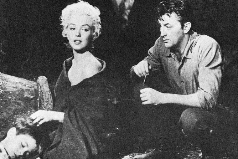 """""""River of no return"""" (La rivière sans retour) d'Otto PREMINGER (Marilyn sur le tournage et photos du film) : ANALYSE et CRITIQUE (part 7) / Quoi qu'il en soit, il est permis de penser que la comédienne n'a jamais été ni meilleure ni plus désirable que dans ce western. Offerte sans fard à l'objectif caressant de Joseph LaSHELLE, elle s'y révèle pour la première fois – et peut-être la dernière - femme sous toutes ses facettes : tantôt femme enfant aveuglée par un premier amour factice ; tantôt piquante et séductrice ; tantôt maternelle face au petit Mark, le ravissant d'une merveilleuse complainte en plein air et rajustant sa tenue vestimentaire devant ses yeux, sans aucune fausse pudeur ; tantôt amante, découvrant ses sentiments au cours d'une scène de massage entrée dans toutes les mémoires cinéphiles, mais qui aurait été tournée par Jean NEGULESCO, après une preview publique assez désastreuse ; loin, très loin, de l'image de fausse ingénue désarmante et charnelle dans laquelle elle resta trop souvent enfermée. C'est peu dire que chacune des chansons qu'elle interprète, tour à tour songeuse (One silver dollar), provocante (I'm gonna file my claim), épanouie (Down in the meadow, donc) ou douloureusement nostalgique (la reprise finale de River of no return) est comme un petit moment de paradis cinégénique..."""