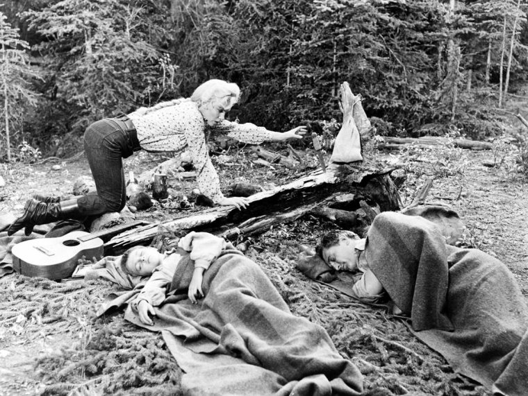 """""""River of no return"""" (La rivière sans retour) d'Otto PREMINGER / ANALYSE et CRITIQUE (part 8) / Western de la plénitude, il est évident que """"Rivière sans retour"""" doit aussi beaucoup au style de caméra de son réalisateur, qui abordait le format du Cinémascope pour la première fois de sa carrière. Immédiatement conquis (hormis """"The man with the golden arm"""" et """"Anatomy of a murder"""" toutes les réussites ultérieures du cinéaste s'exprimeront à travers ce format ou celui, cousin, du SuperPanavision 70) PREMINGER l'utilise comme un écrin pour valoriser, dans de très amples et très lents mouvements d'appareils, la majesté irréelle de cette nature sauvage des Rocheuses, ½uvrant avant tout sur la profondeur de champs pour donner un relief saisissant à ces gorges creusées par le torrent tumultueux ou pour conférer des dimensions sans fins à une vallée encaissée entre deux massifs montagneux. Filmant comme il respire, il sait aussi traduire l'effervescence de cette nouvelle """"Sodome et Gommorrhe"""" (dixit le fidèle acteur """"fordien"""" Arthur SHIELDS dans son éternel emploi de prédicateur) que représente le camp de prospecteurs, découvert jusque dans les moindres strates offertes par l'accumulation géométrique des toiles de tentes dans le cadre, toutes grouillantes de vie, au rythme d'un travelling latéral effréné entrepris de droite à gauche après une courte hésitation et la retenue d'un cheval qui se cabre, surpris par la peur ; du grand art..."""