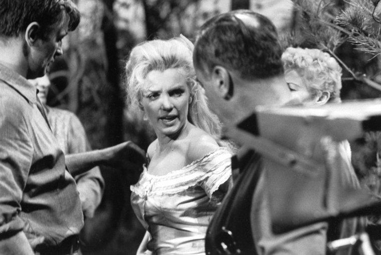 """""""River of no return"""" (La rivière sans retour) d'Otto PREMINGER / CRITIQUE / S'il est loin d'être un titre phare du western, """"Rivière sans retour"""" est surtout l'occasion de voir Marilyn en chanteuse de saloon. Comme souvent dans les films où elle apparaît, de nombreuses scènes sont prétextes à la voir chanter, même si ça tombe comme un cheveu sur la soupe (un peu comme dans certains Disney). Toutefois ces scènes là sont assez réussies et les mélodies plutôt agréables et collant bien avec l'atmosphère du film.  Le vrai point central de ce film est la relation amour-haine entre Marilyn et le personnage de Robert MITCHUM, véritable macho comme on n'oserait plus en montrer aujourd'hui, usant de sa force pour se faire obéir, traitant les femmes comme des bobonnes et décidant ce qu'elle doit faire ou non. Et en bonne femme soumise Marilyn dit oui à tout ou presque. Au delà de cet aspect un peu douteux aujourd'hui, on peut y voir la complexité des relations entre un homme dévoué à l'éducation de son fils et cherchant à rattraper un passé houleux, et une femme soumise qui s'accroche à son ordure de petit ami en fermant les yeux sur ses méfaits en lui cherchant des excuses, et lui donnant ses maigres gains obtenus en chantant dans les saloons. Son émancipation va se réaliser au travers des aventures qu'elle va vivre dans la nature sauvage."""