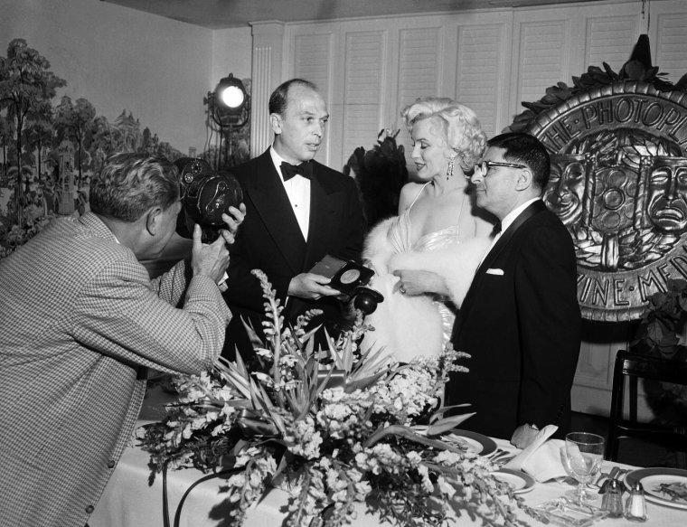 """1954, Marilyn accompagnée de son ami Sidney SKOLSKY reçoit le prix """"Photoplay Magazine Award"""" de """"The Most Popular Actress of 1953"""" (""""La meilleure actrice populaire de l'année 1953"""") pour ses rôles dans «Gentlemen prefer blonds» (""""Les Hommes préfèrent les blondes"""") et «How to marry a millionaire» (""""Comment épouser un millionaire""""). La remise de prix eut lieu dans une salle du Beverly Hills Hotel. De nombreuses stars participeront à la soirée, notamment l'acteur Alan LADD avec lequel Marilyn pose. / Marilyn porte la même robe qu'en 1953 lors d'un gala de bienfaisance avec Jack BENNY / part 2"""