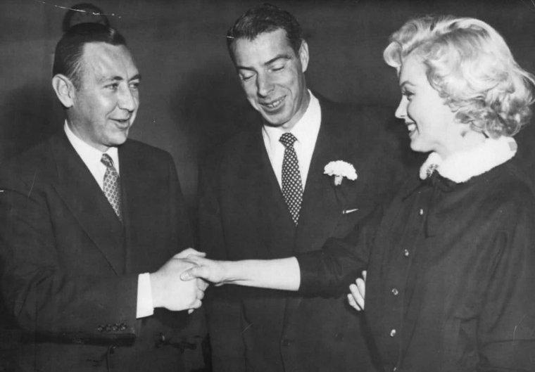 """14 JANVIER 1954, Marilyn et Joe DiMAGGIO se marient civilement à l'Hôtel de ville de San-Francisco (Polk street). Elle porte à l'occasion un tailleur marron chocolat avec un col d'hermine blanche. Joe voulait épouser Marilyn religieusement, mais l'archevêque de San Francisco, John MITTY, refusa de reconnaître la validité de son divorce avec Dorothy ARNOLDS, sa première épouse. Il n'y eut donc qu'un mariage civil.  Ils y pensaient bien sûr depuis un certain temps, mais ne prirent la décision que deux jours avant. Ils souhaitaient un mariage aussi discret que possible, et Marilyn ne prévint le studio qu'une heure avant la cérémonie. Malgré cela plus de cent journalistes et reporters envahirent l'entrée et les couloirs de l'hôtel de ville.  Elle n'avait pas d'invités personnels; seule la famille et les amis de Joe assistaient à la cérémonie, célébrée par l'officier municipal, le juge Charles S.PERRY.  La cérémonie débuta à 13h48 et se termina trois minutes plus tard. Le témoin de Joe était Reno BARSOCCHINI ; les autres invités étaient Jean et Lefty O'DOUL, Tom DiMAGGIO et sa femme Lee. A la sortie de la mairie, ils furent assaillis pas les journalistes puis ils sautèrent dans la Cadillac bleu nuit de Joe en route pour leur lune de miel : une nuit au """"Clifton Motel"""", à Paso Robles, puis deux semaines dans une maison cachée dans la montagne (la maison de l'avocat de Marilyn, Lloyd WRIGHT), en dehors d'Idyllwild, près de Palm Springs. La vie fut aussi difficile qu'avant le mariage, bien que tous deux étaient prêts à des concessions mutuelles.  Joe était très méticuleux, aussi bien chez lui que dans ses affaires; Marilyn était exactement le contraire. Il préférait la vie calme  à San Francisco, elle avait besoin de Los Angeles; il était taciturne et réservé, elle était impulsive et sujette aux éclats ; il aimait passer son temps avec sa famille et ses amis ou passer une soirée à regarder la télévision, elle, qui avait abandonné les soirées hollywoodiennes, souhaitait des s"""