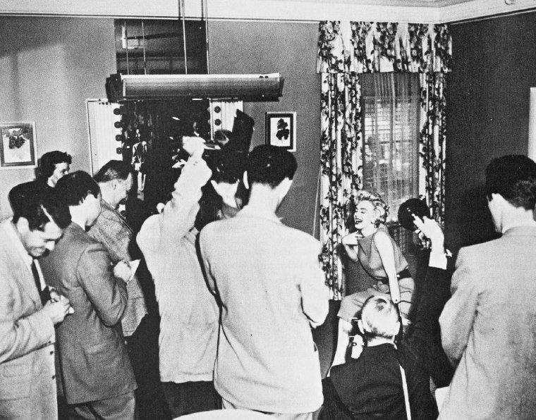 """Le 15 avril 1954, une séance de chant est organisée devant la presse à Hollywood pour célébrer le retour de Marilyn à la Fox. Marilyn répète avec son professeur Hal SCHAEFER avec qui elle collabora pour ses chansons dans """"Gentlemen prefer Blondes"""" (Les Hommes préfèrent les blondes) en 1953, """"River of no return"""" (La Rivière sans retour) en 1954 puis pour """"There's no business like show business"""" (La Joyeuse Parade) en 1954. Après la prestation, Marilyn reçoit un trophée: le """"National Movie Poll Award"""" des mains de William WILKERSON, représentant le """"Hollywood reporter"""". Lors de cette séance de chant organisée avec la presse, Marilyn annonça qu'elle et son époux Joe DiMAGGIO souhaitaient fonder une famille """"aussi vite que possible"""". """"Je ne le suis pas encore, mais je le veux, être enceinte je veux dire"""". Elle déclara qu'avec Joe , ils vivaient à San Fransisco et qu'ils loueraient une maison à Hollywood lorsqu'elle sera en tournage."""