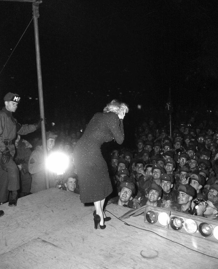 """Elle part ensuite terminer la journée à la base de la """"25th Marine Division"""". Le régiment lui remet un prix spécial, sous forme de certificat, la déclarant """"Membre d'honneur de la 25ème Division"""". Et le sergent Guy MORGAN lui remet une large écharpe en satin avec le logo de leur régiment.  Puis Marilyn tape dans une batte de Baseball, le sport de son mari Joe DiMAGGIO, avec la complicité de joueurs sud-coréens, vêtus du fameux ensemble à rayures représentatifs de ce sport si populaire pour les américains.  En début de soirée, elle se produit sur scène avec son orchestre, qui a lieu à l'abri, dans une grande tente."""