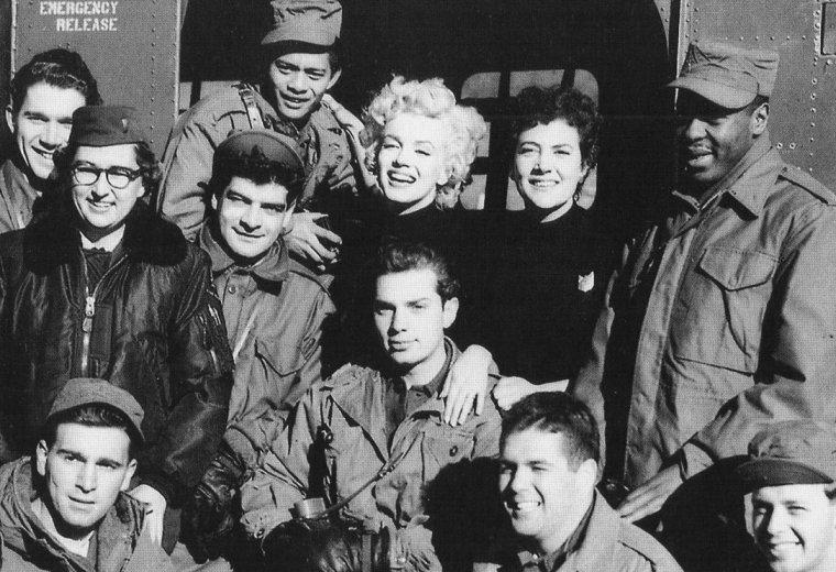 """Elle est ensuite invitée par les officiers du """"NCO Club"""" de la """"2nd Division"""" pour prendre un goûter. Au menu: gros gâteau de crème avec l'inscription """"Thank You Mrs MONROE"""", coupée par Marilyn, et café. Les soldats raconteront qu'elle avait un bon appétit. Marilyn n'a pas changé de tenue et porte toujours son pantalon kaki avec hautes rangers et pull noir. Jean O'DOUL, qui l'accompagne dans ses déplacements, est d'ailleurs vêtue de la même façon; et Marilyn lui a même prêté l'écharpe que la """"25ème Division"""" lui a offerte la veille.  Puis elle se prête au jeu des poses photos avec l'équipe de soldats qui était de service ce jour là (""""The Service Quarters"""")."""