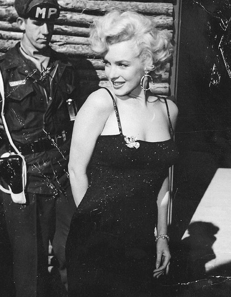"""Puis elle visite la base, d'abord debout dans une jeep, puis à pied. Marilyn porte cette fois-ci sa robe en laine aux manches trois-quarts. Elle enfilera ensuite le blouson par-dessus. Le soir, elle est invitée au dîner organisé par la """"2nde Division"""". Marilyn refusera de se faire servir, et comme dans un self-service, elle portera son plateau devant les plats des cuisiniers et attendra dans la file d'attente, avec les soldats, pour obtenir son assiette. Avec Jean O' DOUL, elles iront ensuite au service cuisine pour se transformer en serveuse, portant pour l'occasion la petite toque blanche sur la tête, et servir les assiettes des soldats."""