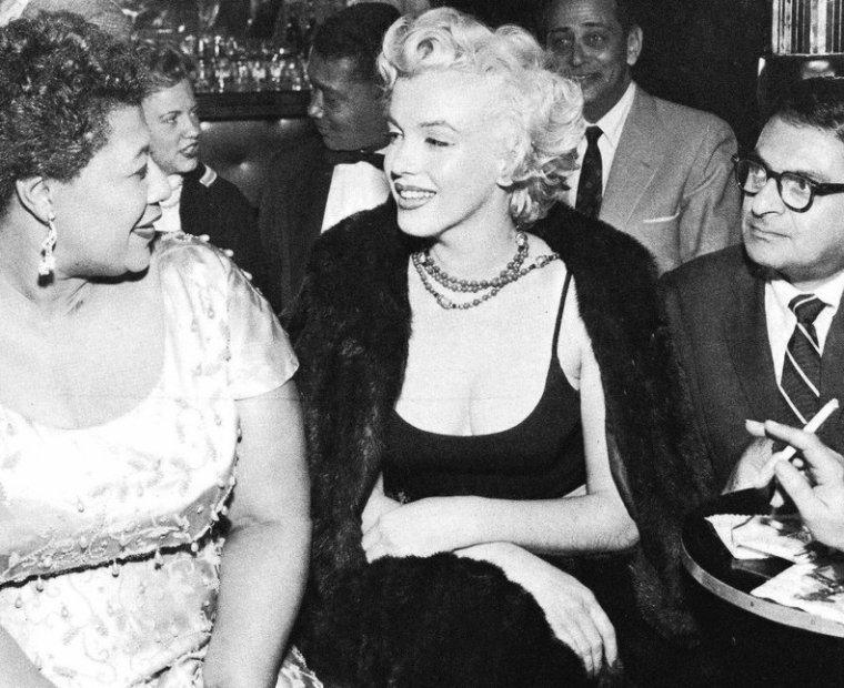 """1954, Marilyn adorait le Jazz. Elle discute ici avec sa chanteuse préférée Ella FITZGERALD dans un club de Jazz -""""Le Mocambo""""- à Hollywood : """"Le Tiffany Club"""" le 19 novembre 1954. Pour cette soirée, Marilyn était accompagnée de son ami l'écrivain Sidney SKOLSKY. Un jour, apprenant qu' Ella FITZGERALD ne pouvait pas chanter dans une boîte à la mode (""""Le Mocambo"""" à Los Angeles) parce que Noire, Marilyn téléphona personnellement au patron et lui dit qu'elle réserverait chaque soir une table au premier rang s'il revenait sur sa décision. Et, chaque soir où Ella FITZGERALD chanta, Marilyn honora sa promesse. Ella raconta plus tard : """"Je dois à Marilyn MONROE une vraie dette. Ce fut grâce à elle que je jouai au """"Mocambo"""", un club de nuit très populaire à la fin des années 1950. Elle appela personnellement le propriétaire du """"Mocambo"""" et lui raconta qu'elle voulait m'y voir engagée immédiatement, et s'il le faisait, elle réserverait une table au premier rang pour chaque soirée. Elle lui dit, et c'est la vérité, que de par son statut de star, que la presse se montrerait féroce. Le propriétaire accepta, et Marilyn était là, à la première table, chaque soir. La presse laissa tombé... Après ça, je n'ai jamais plus eu à jouer dans de petit club de jazz. Elle était une femme insolite, un peu en avance sur son temps. Et elle ne le savait pas."""""""
