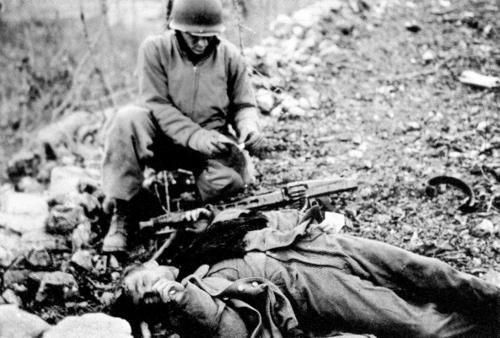 Un soldat américain inspecte les papiers d'un soldat allemand mort au printemps de 1945.