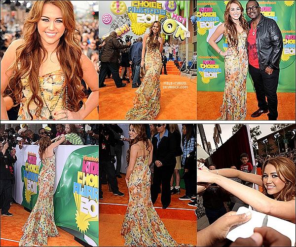 .  .  ___ _♦ APPARENCES_ __ Miley était aux Kids Choice Awards cette nuit de 2avril qui a eu lieu au Galen Center de LA. .  Comme chaque année, Miley Cyrus était comme toutes les jeunes stars à la cérémonie des Kids Choice Awards réalisé par Nickelodeon pour les enfants. Elle était magnifique! Nous retrouvons à cette cérémonie l'ancienne Miley Cyrus qui s'habille pleines de couleurs et qui est tant convoitée par tout les fans. Un énorme TOP pour la longue robe à fleur associée aux couleurs des tapis oranges (exprès?) et pour sa coiffure simple mais jolie. Je trouve qu'elle a fait un très gros effort par rapport à l'année dernière où elle avait seulement mis un long tee-shirt gris et un legging noir. Et toi t'en penses quoi?   .  .