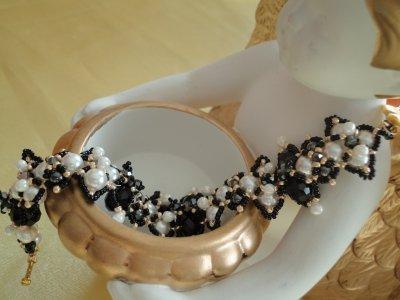 une autre photo, où l'on voit les perles nacrées blanches, les perles rondes en hématite ainsi que des perles noires en crystal