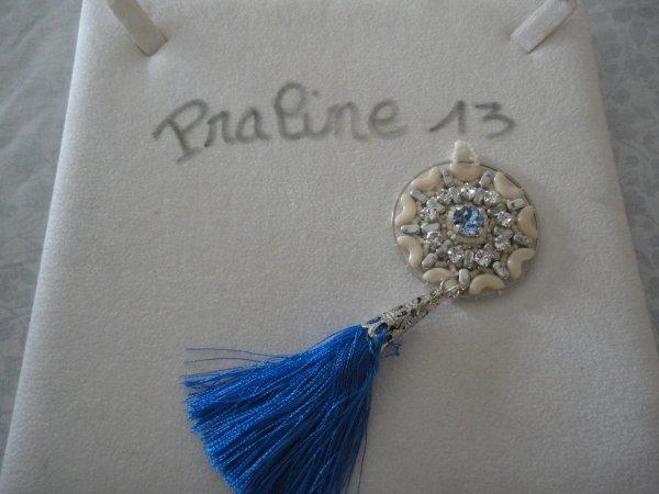 Un autre pendentif de Puca, monté sur un anneau avec un joli pompon bleu