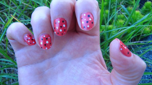 Nail-art à pois blanc et marron sur rouge brillant