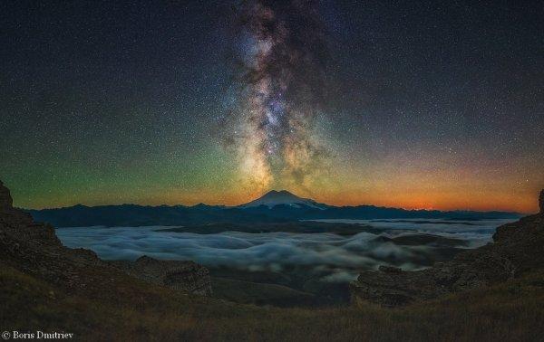 L'IMAGE DU JOUR est de Boris Dmitriev. Cette superbe photo montre le plus haut sommet d'Europe, le mont Elbrouz, dans le Caucase, un ancien volcan qui semble cracher la Voie lactée devant l'objectif de Dmitriev. Le Mont Elbrouz culmine à 5642 mètres, le point culminant d'une chaîne de montagnes située dans le nord du Caucase, en Russie. Autant dire que son sommet reste difficile d'accès en raison des conditions climatiques, ce qui explique qu'il ne fut vaincu qu'en 1874. Si ce volcan est aujourd'hui endormi, cela n'a pas toujours été le cas. Selon la mythologie grecque c'est au sommet du mont Elbrouz que le titan Prométhée aurait été attaché par Zeus après avoir désobéi au roi des dieux en offrant le feu aux hommes. (Sources B. Dmitriev-JBF)