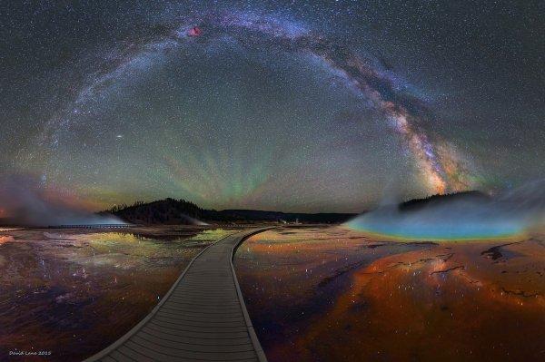 L'IMAGE DU JOUR : David Lane, astronome amateur a réalisé ce panorama depuis le parc de Yellowstone, aux États-Unis. Il met en scène plusieurs phénomènes géophysiques. Les sources d'eau chaude témoignent d'une activité volcanique hors du commun. Tous les 600 000 ans environ, une chambre magmatique de 15 000 à 20 000 kilomètres cubes, située à une dizaine de kilomètres de profondeur, est totalement remplie. Il en résulte des éruptions explosives, mille fois plus fortes que celle du mont Saint Helens en 1980 ! La caldeira actuelle de 45x85 km témoigne de l'ampleur de la catastrophe. Ce paysage remarquable est donc éphémère. La dernière éruption a eu lieu voici 640 000 ans, ce qui signifie que la chambre magmatique est proche de la saturation. La prochaine éruption est donc imminente... à l'échelle géologique. En attendant, la Voie lactée se reflète paisiblement dans les mares d'eau chaude, avec à l'avant-plan les ondulations vertes des airglows. Il s'agit de molécules d'oxygènes excitées, qui réémettent leur énergie la nuit. (Source D.Lane-AFA)