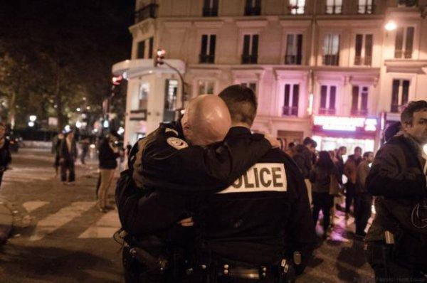 """DEUIL !! La photo a été prise aux alentours de 21h devant le bar """"À la Bonne Bière"""", au coin des rues de la Fontaine au Roi et du Faubourg du Temple (XIe), où cinq personnes ont été tuées vendredi soir. """"J'ai vu deux policiers qui étaient en train de se recueillir, ils se sont accordés un instant à l'écart et l'un d'eux a craqué"""", raconte le photographe Benjamin Filarski, qui a capturé ce dimanche 15 novembre au soir un moment d'émotion particulier entre deux policiers. Aujourd'hui nous pleurons et nous prions... ensemble, de Lourdes à Paris, de France aux États Unis...! Mais toujours avec plein d'Espérance, d'Amour et de Paix ! (Les membres de l'Astro Club Lourdais)"""