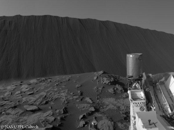 LA PHOTO DU JOUR : Depuis quelques semaines le rover martien CURIOSITY est au pied des dunes de Bagnold, des édifices de sable hauts de plusieurs mètres et très sombres en raison de leur forte teneur en olivine et en pyroxène. Ces dunes se déplacent sous l'effet des vents martiens. Les observations menées depuis l'orbiteur Mars Reconnaissance Orbiter (MRO) ont montré que ces dunes de sable sur Mars se déplacent d'environ 2 mètres par année martienne (l'année martienne vaut 687 jours terrestres), Ces dunes sont poussées par le vent comme celles que l'on observe par exemple à Windhoek, une région du désert de Namibie. Mais sur Mars la pression atmosphérique est 170 fois plus faible que sur Terre et la gravité est également moins élevée : il sera donc très intéressant d'acquérir des informations « in situ » pour mieux comprendre les effets de l'érosion éolienne à l'occasion de ce qui est la première étude de dunes de sable extraterrestres. (Sources NASA-MRO-JBF) Sur cette image transmise par CURIOSITY on peut voir les traces de petites avalanches de sable qui sculptent la pente d'une dune noire exposée au vent !