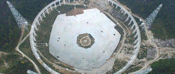 """L'IMAGE DU JOUR : UN RADIOTÉLESCOPE GÉANT CHINOIS !! Le plus grand Radiotélescope du monde, nommé Fast, va être mis en marche en 2016. Objectif : """"chercher une forme de vie intelligente en dehors de notre galaxie"""". En Chine, tout est à l'image du pays et de ses 1,4 milliard d'habitants. Alors, quand l'empire du Milieu décide de mettre au point un télescope, ce n'est pas pour créer une vulgaire longue vue. Conceptualisée en 1990, la construction du télescope Fast a débuté en 2011 et devrait se terminer cette année. Avec 500 mètres de diamètre, Fast relègue son homologue de Arecibo (Porto Rico) et ses 300 mètres de diamètre au rang de deuxième plus grand télescope du monde ! La grandeur de Fast est telle que les autorités de la province de Guizhou ont été amenées à déloger les 9 110 résidents qui vivaient dans un rayon de cinq kilomètres autour de l'installation. En effet, son objectif est de « chercher une forme de vie intelligente en dehors de notre galaxie », rappelle Wu Xiangping, directeur de la Société astronomique chinoise. Et pour cela, les autorités locales ont besoin de « créer un environnement électromagnétique sain ». D'où ce déplacement massif de population. Les autorités précisent néanmoins que chacun des délogés recevra 12 000 yuans (1 650 euros) de dédommagement. (Source Le Point)"""