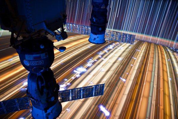 LA PHOTO DU JOUR : Filés D'étoiles, les lumières de la ville et des éclairs pris depuis la station Spatiale Internationale, formant un arrière-plan pour l'ISS et le vaisseau Soyouz, par l'astronaute Don Pettit, (Sources NASA-ESA-expedition 31 en février 2015)