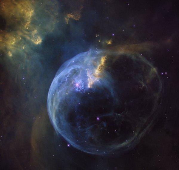 L'IMAGE DU JOUR : HUBBLE OBSERVE LA NÉBULEUSE DE LA BULLE !! La Nébuleuse de la Bulle a été découverte en 1787 par le grand astronome, William Herschel. Apparu comme rien de plus qu'une bavure noire et blanche faible dans l'oculaire de son télescope. Ici Hubble l'observe avec un gain de couleurs des plus magnifiques. La Nébuleuse de la Bulle est vraiment une bulle. Elle est soufflée dans cette forme par l'étoile brillante connue comme SAO20575, qui est juste à gauche du centre dans cette image. C'est une étoile géante de 10-20 fois la masse du Soleil. L'étoile est comme une pompe d'un torrent effrayant de rayonnement ultraviolet, causant les gaz environnants à rougeoyer comme une lumière fluorescente. Mais ce n'est pas ce rayonnement ultraviolet qui fait la bulle, c'est le vent stellaire de l'étoile SAO20575 qui crée cette bulle. Un vent stellaire est un flux haut débit de particules filant loin de l'étoile. Comme ils entrent en collision avec les atomes de gaz et les molécules dans le nuage environnant ils les repoussent, créant cette bulle lumineuse. A 8.000 années de distance, la nébuleuse atteint maintenant environ 10 années-lumière de diamètre et continue à s'étendre à plus de 100000 km/h. (Sources NASA-HUBBLE)