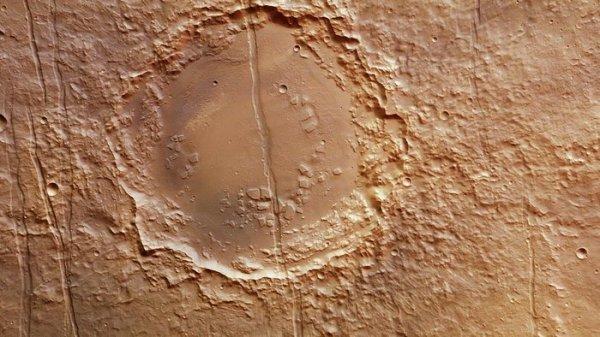 L'IMAGE DU JOUR : un cratère sur Mars dans la région de Memnonia Fossae Un réseau de vastes lignes de faille coupe cette région de Mars, au niveau de ce cratère antique. Le réseau de faille est probablement lié à la formation du Bombement de la région de Tharsis, une région à l'est qui abrite plusieurs grands volcans, y compris le Mont Olympe. Les volumes énormes de lave qui ont éclaté de ces volcans dans le passé ont été déposés sur la surface, développant des couches épaisses. La charge imposée à la croûte de Mars par la lave a abouti à la formation de ces larges systèmes de fractures. Cette large bande de 1.5km coupe ce cratère dans cette image. (Source ESA)