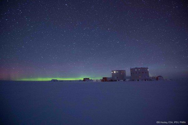 L'IMAGE DU JOUR : LA BASE SCIENTIFIQUE CONCORDIA se trouve sur un plateau de 3200 m au-dessus du niveau de la mer. Un endroit des extrêmes, les températures peuvent descendre jusqu'à -80 ° C en hiver, et le soleil ne se lève pas au-dessus de l'horizon en hiver, ce qui oblige l'équipage à vivre dans l'isolement, sans la lumière du soleil pendant quatre mois de l'année. Son isolement offre aux scientifiques un emplacement unique pour mener des recherches loin de la civilisation dans de nombreuses disciplines. L'atmosphère mince, un ciel clair et zéro pollution lumineuse autour de Concordia en font un lieu idéal pour observer l'Univers - que cette image montre avec une aurore et un ciel étoilé. Pour l'ESA, l'isolement et les conditions météorologiques extrêmes offrent des parallèles intéressants avec les vols spatiaux et vivre sur une autre planète. Chaque année, un médecin ESA-parrainé rejoint l'équipage de la station italo-française pour surveiller et exécuter des expériences sur l'équipage. (Sources ESA-BH)