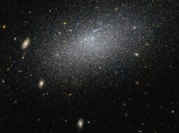 L'IMAGE DU JOUR : UNE GALAXIE PRISE PAR HUBBLE. Le filet d'étoiles dispersées à travers cette image forme une galaxie appelée UGC 4879, galaxie naine irrégulière (comme son nom l'indique, les galaxies de ce type sont un peu plus petit que leurs cousines cosmiques, il y manque le tourbillon majestueux d'une spirale ou la cohérence d'un elliptique). Cette galaxie est également très isolée. Il y a environ 2,3 millions d'années lumière entre UGC 4879 et son plus proche voisin, Leo A, qui est à la même distance qu'occupe la galaxie d'Andromède et la Voie lactée. Les études de UGC 4879 ont révélé une quantité importante de formation d'étoiles dans les 4 premiers milliards d'années après le Big Bang, suivie par une étrange accalmie de neuf milliards d'années dans la formation des étoiles, a pris fin il y a 1 milliard d'années par un plus récent rallumage. La raison de ce comportement, cependant, reste mystérieuse, et la galaxie solitaire continue de fournir suffisamment de données pour les astronomes qui cherchent à comprendre les mystères complexes de la naissance d'étoiles à travers l'Univers. (Source NASA-HUBBLE)