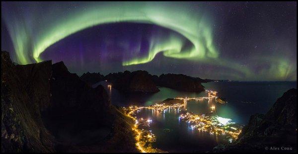 L'IMAGE DU JOUR : AURORE BORÉALE, dans l'archipel norvégien des Lofoten, reçoit souvent la visite d'aurores boréales. Sur cette image prise depuis un sommet du village de Reine, surplombant la scène, le rideau auroral semble créer une étrange tension avec les lumières de la côte. Perspective moderne sur la nuit du monde, cette image a remporté le premier prix du concours photo 2016 de l'association « The World at Night ». (Sources The World at Night-CdH)