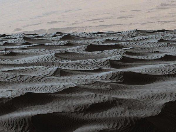 L'IMAGE DU JOUR : DES DUNES DE MARTIENNES, image du robot Curiosity sur la planète Mars présente un paysage saisissant ! Dans une étude publiée le 1er juillet 2016 dans la revue américaine Science, une équipe de planétologues montre qu'il recèle aussi des informations intéressantes sur l'épaisseur de l'atmosphère martienne. Sur Terre, le sable forme de grandes dunes – typiquement de plusieurs dizaines de mètres –, mais aussi des petites rides à leur surface. Celles-ci forment des lignes sinueuses séparées de moins de 30 cm, formées par la collision de grains de sable portés par le vent avec la surface des dunes. Sur Mars, ce type de formations existe aussi, mais c'est un autre mécanisme qui est à l'origine des dunes que Curiosity a immortalisées sur les flancs du mont Sharp : le même qui crée les rides que l'on observe sur les fonds sablonneux de nos plages, où les grains de sable ne sont pas portés par le vent, mais entraînés par le courant. Dans ce processus, la taille des rides est inversement proportionnelle à la densité du fluide qui entraîne le sable. Sur la planète rouge, le fluide est l'atmosphère martienne ! Comme elle est actuellement très peu dense, elle forme des rides de 3 m, énormes selon nos critères terrestres. Les planétologues cherchent maintenant des champs de dunes similaires, mais fossiles, pour estimer la densité de l'atmosphère de Mars dans le passé. Leurs premiers résultats montrent qu'elle se serait très tôt amoindrie ! (Sources NASA-C&E)