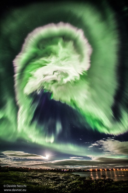 L'IMAGE DU JOUR : Une aurore d'Halloween très impressionnante sur l'Islande. Ce tourbillon dans des nuances d'obscurité et d'enchevêtrement vert pâle avec des taches lumineuses de blanc, créant une spirale nouée ressemblant un peu à un serpent céleste se tordant à travers le ciel, au-dessus de la ville endormie dessous ! Elle peut sembler effrayante, mais cette image montre quelque chose d'assez banale aux latitudes du nord et du sud de la Terre. Les éclairs de vert dans le ciel sont une aurore, vue quand de grandes rafales de particules atomiques énergétiques sortent du Soleil et frappent l'atmosphère de la Terre. L'effet n'est observé qu'aux latitudes polaires car les particules chargées se déplacent vers la Terre le long des lignes de champ magnétique qui rencontrent notre planète à ses pôles. Les aurores sont la manifestation la plus visible de l'effet du Soleil sur la Terre. Cette image montre une ville au sud de l'Islande nommée Selfoss, sur la rivière Ölfusá (visible au premier plan). Elle a été prise par le photographe Davide Necchi le 27 août 2015. Cette aurore particulière a été liée à une tempête solaire, qui a provoqué un déversement particulièrement important et soudain de particules dans notre atmosphère. En conséquence, les lumières étaient intenses et exceptionnellement brillantes, apparaissant brusquement dans le ciel du soir avant qu'il ne fût complètement sombre. En fait, l'aurore était si brillante que Davide a opté pour un temps d'exposition relativement court de 3 secondes. Necchi a utilisé une caméra Canon 5D Mark II avec un objectif de 14 mm f2.8. Cette image a une ISO de 1600, et aucun filtre n'a été appliqué. La pleine lune lumineuse est également visible dans le cadre, suspendu sous une couche de nuage. (Sources ESA-Necchi)