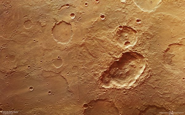 L'IMAGE DU JOUR : Triple cratère dans Terra Sirenum sur Mars. Une image des anciennes hautes terres du sud de Mars mettant en évidence un triple cratère, la dépression allongée juste au centre. Mesurant environ 45 x 24 km, on pense que le cratère a été créé par la collision d'un « triple amortisseur », peut-être d'une météorite qui a éclaté en trois après avoir pénétré dans l'atmosphère. La région a été photographiée par la caméra stéréo haute résolution par la sonde Mars Express. La résolution au sol est d'environ 22 m par pixel. (Sources ESA-NASA-MarsExpress)