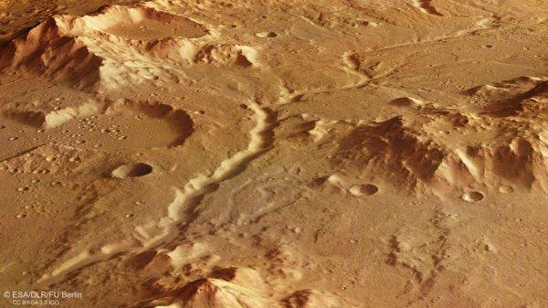 L'IMAGE DU JOUR : LA RÉGION DE LYBIE MONTES SUR MARS PAR LA SONDE MARS EXPRESS ! Vue en perspective faisant le tour d'un canal de rivière ancien et desséché dans la région de Libye Montes, près de l'équateur sur Mars. La vallée serpente entre des montagnes anciennement alimentée par de nombreux affluents issus des précipitations et du ruissellement de surface. À gauche, on peut voir une partie d'un cratère et son plancher doux. (Sources ESA-NASA-MARSEXPRESS)