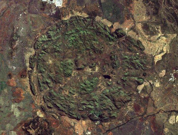 LA TERRE VUE DE L'ESPACE : PILANESBERG, Afrique du Sud. La structure circulaire qui domine cette image Sentinel-2 est Pilanesberg, résultat d'une activité géologique depuis plus d'un milliard d'années. Une fois un complexe volcanique massif de plus de 7000 m de haut, des millions d'années d'érosion ont façonné le paysage à ce qu'il est aujourd'hui: des anneaux concentriques de collines qui s'élèvent de la plaine environnante, avec un diamètre de quelque 25 km. Une grande partie de Pilanesberg est une réserve protégée. Dans la structure circulaire, nous pouvons voir quelques plans d'eau, le plus grand étant Mankwe près du centre. Avant que cette zone ne soit une réserve, les agriculteurs ont construit ce barrage pour créer ce lac, mais aujourd'hui, il attire les touristes qui cherchent à repérer la faune. Les terres situées à l'extérieur de Pilanesberg sont tachées d'infrastructures telles que les bâtiments, les routes et même le stade de football (en haut à droite). L'Afrique du Sud est le premier producteur mondial de platine, et un certain nombre de mines entourent le parc - comme la zone lumineuse au sommet de l'image, ou la zone carrée en bas.(Source satellite Copernic-Sentinel-2B ESA).