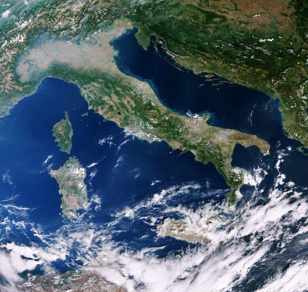 LA TERRE VUE DE L'ESPACE : ITALIE ET MEDITERRANEE par le satellite Copernicus Sentinel-3A. D'est en ouest, l'image montre les îles de la Corse et de la Sardaigne dans la mer Méditerranée, l'Italie et à travers la mer Adriatique jusqu'en Croatie, en Bosnie-Herzégovine, en Serbie et à l'ouest de la Roumanie. Au nord et partiellement obscurci par les nuages, se trouvent l'Allemagne, la Suisse, l'Autriche et les Alpes. Au sud des Alpes, la brume plane sur la vallée du Pô en Italie. En suivant la rivière Po à l'est, les sédiments qu'elle transporte peuvent être vus en entrant dans la mer Adriatique. En fait, les sédiments bordent la majeure partie de la côte orientale de l'Italie, ce qui lui donne un cadre bleu verdâtre, tandis que la côte ouest est essentiellement exempte de sédiments. (Sources ESA-COPERNIC-SENTINEL)