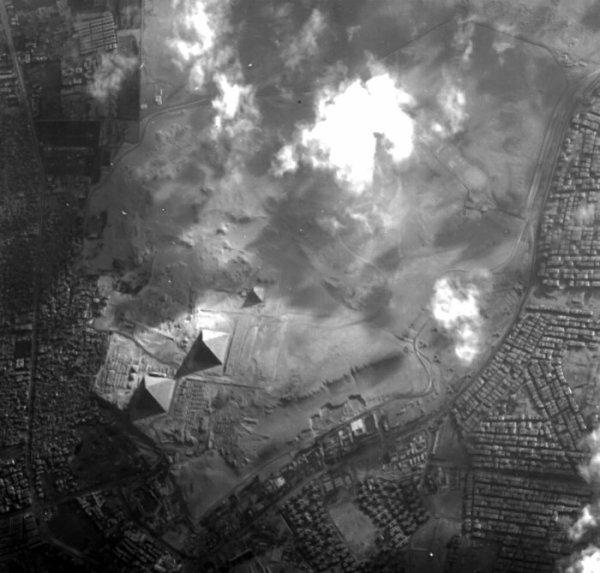 LA TERRE VUE DE L'ESPACE : VUE SUR LES GRANDES PYRAMIDES DE GIZEH par le minisatellite Proba-1 de l'ESA. Au centre de l'image la plus petite Pyramide de Menkaure, en bas et à gauche la Pyramide de Khéphren, et la Grande Pyramide de Gizeh, la plus grande et la plus ancienne des trois. Trois pyramides plus petites sont adjacentes à la Pyramide Menkaure. Le plateau de Gizeh est situé au bord du Caire, bordé de banlieues. Proba-1 permet d'acquérir des images en résolution 5m en noir et blanc. (Sources ESA-PROBA-1)
