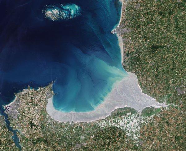 LA TERRE VUE DE L'ESPACE : LE MONT SAINT-MICHEL, VU PAR LE SATELLITE COPERNICUS SENTINEL-2. Située entre la Bretagne à l'ouest et la Normandie à l'est, cette baie remarquable, inscrite au patrimoine mondial de l'UNESCO, est l'une des plus grandes marées d'Europe continentale. Il peut y avoir jusqu'à 15 m de différence entre les basses et les hautes eaux. Lorsque les marées printanières atteignent un sommet, la mer recule d'environ 15 km de la côte et quand elle revient, elle le fait très rapidement, ce qui en fait un endroit dangereux. Sentinel-2 a capturé cette image quand la marée était sortie, de sorte que la vaste zone de dunes de sable est exposée coupée par des méandres d'eau peu profonde. Trois rivières se déversent dans la baie: le Couesnon, la Sée et la Sélune. Le célèbre îlot rocheux du Mont Saint-Michel, visible comme une petite tache sombre au sud de la baie, se trouve à environ 1 km de l'embouchure du Couesnon, et abrite un monastère et un village bénédictins. Une campagne majeure a permis au Mont-Saint-Michel de conserver son caractère maritime et de rester une île. Le fleuve principal dans la baie, le Couesnon, par exemple, est laissé plus libre de sorte que les sédiments sont emportés vers la mer.(Sources ESA-Copernic Sentinel)