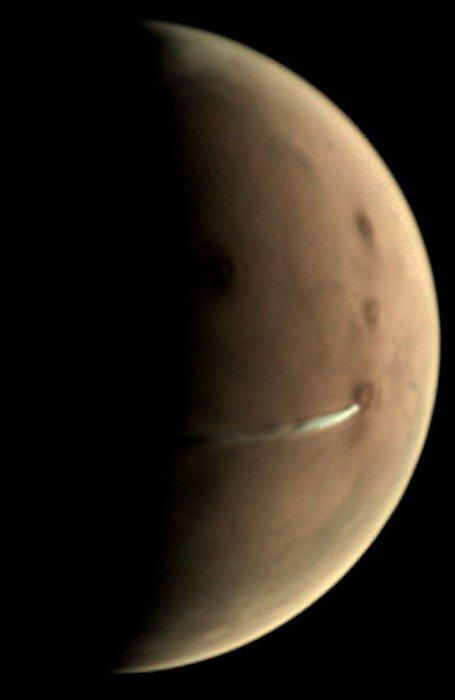 L'IMAGE & L'INFO ASTRO DU JOUR : FORMATION NUAGEUSE SUR MARS ! Depuis le 13 septembre, Mars Express, de l'ESA, observe l'évolution d'une formation nuageuse allongée planant à proximité du volcan Arsia Mons, haut de 20 km, proche de l'équateur de la planète. En dépit de son emplacement, cette caractéristique atmosphérique n'est pas liée à l'activité volcanique mais est plutôt un nuage de glace d'eau entraîné par l'influence de la pente sous le vent du volcan sur le flux d'air, ce que les scientifiques appellent un nuage orographique ou sous le vent, phénomène régulier dans cette région. Le nuage est visible dans cette vue prise le 10 octobre par la caméra de surveillance visuelle (VMC) de Mars Express - qui l'a reproduite des centaines de fois au cours des dernières semaines - en tant que trait blanc allongé s'étendant sur 1500 km à l'ouest d'Arsia Mons. À titre de comparaison, le volcan en forme de cône a un diamètre d'environ 250 km. Mars vient de vivre son solstice d'hiver dans l'hémisphère nord le 16 octobre. Dans les mois qui ont précédé le solstice, la plupart des activités nuageuses ont disparu sur de grands volcans comme Arsia Mons; son sommet est couvert de nuages pendant le reste de l'année martienne. Cependant, il est connu qu'un nuage de glace d'eau récurrent, comme celui montré dans cette image, se forme le long du flanc sud-ouest de ce volcan - il avait déjà été observé par Mars Express et d'autres missions en 2009, 2012 et 2015. (Source ESA-ME-NASA)